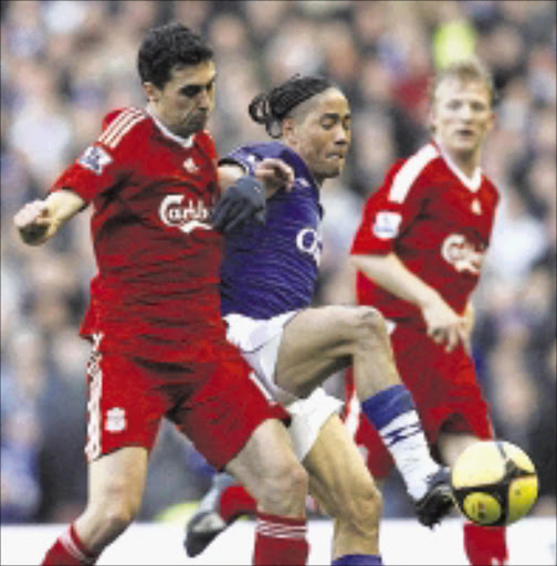TUSSLE: Everton's Steven Pienaar,  centre, fights for the ball against Liverpool's Alvaro Arbeloa, left, while Dirk Kuyt, right, looks on during their English FA Cup fourth round soccer match at Anfield Stadium yesterday.  25/01/2009. Pic. Paul Thomas. © AP