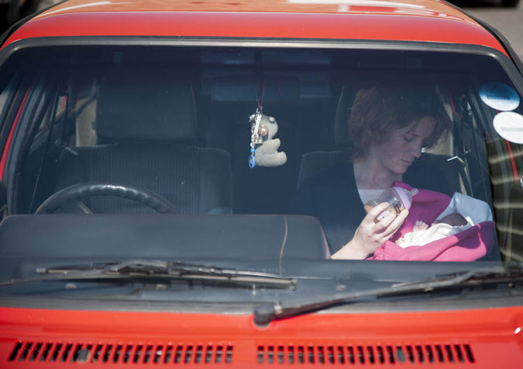 A woman feeding her baby in a car.