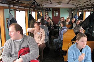 Photo: Uczestnicy Zlotu siedzący w zabytkowym wagonie obserwują okolicę podczas jazdy na kolejowym szlaku