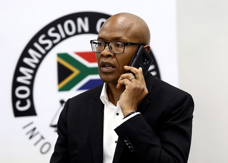Mzwanele Manyi talks on his phone at the Zondo state capture commission on Wednesday. Picture: MASI LOSI