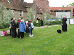 Photo: An Anglican priest photographs British pilgrims at Walsingham.