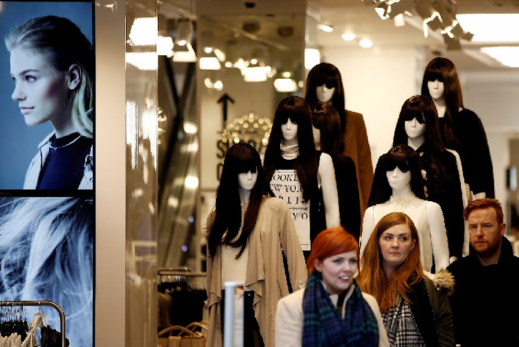 Customers pass mannequins displaying women's clothes as they exit a New Look fashion store in London, the UK. File picture: BLOOMBERG/SIMON DAWSON