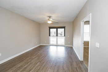 Vacant apartment living room with wood floor, bedroom door on right side, and double patio doors