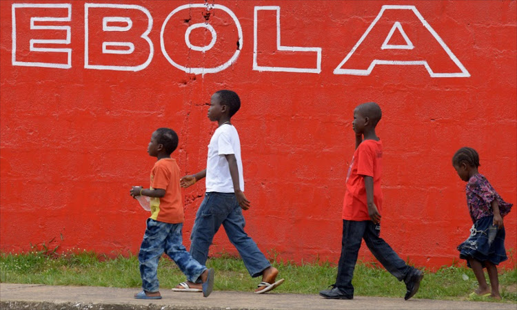 (FILES) This file photo taken on August 31, 2014 showing children walk past a slogan painted on a wall reading