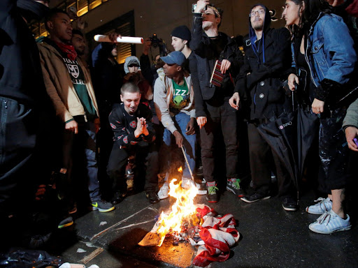 Protesters burn a US flag outside Trump Tower following President-elect Donald Trump's election victory in Manhattan, New York, US on November 9.