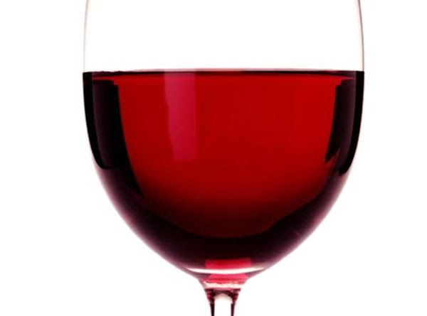 RED WINE GLASS A clear, thin, stemmed glass with a round bowl tapering inward at...
