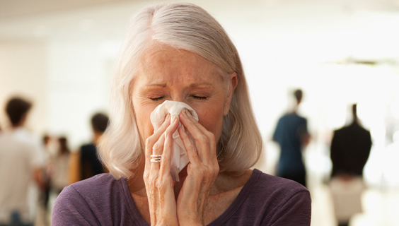 An older woman blowing her nose.