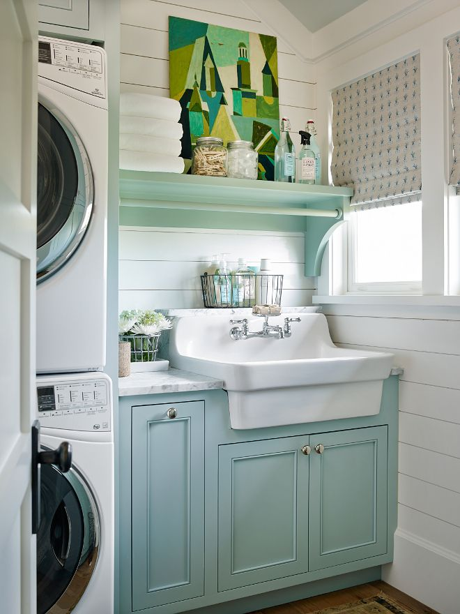 tiny laundry room with light blue cabinets and stacked washer and dryer. white shiplap walls and farmhouse sink give the room a rustic and vintage look