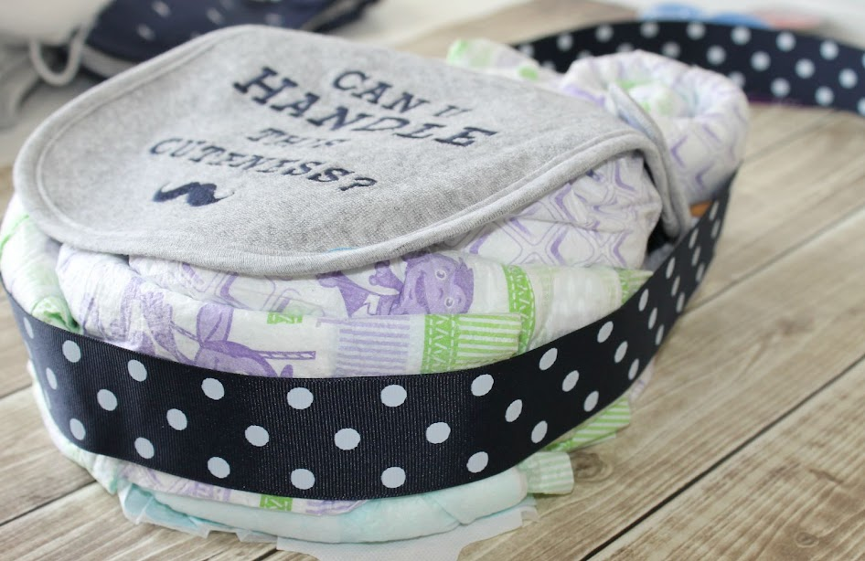 Wrap a wide, coordinating ribbon around the body and eyes of the owl diaper cake to hide your rubber bands