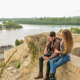 Modern young couple using their mobile phone near the river by Vera Arsic - People Couples ( young women, romance, two people, heterosexual couple, friendship, city life, togetherness, young adult, social networking, river bank, selfie, model, connection, communication, smiling, attractive, smart phone, telephone, lovers, lifestyles, girlfriend, enjoyment, color image, adult, photography, city, boyfriend, affectionate, modern, romantic, happiness, joy, dating, flirting, caucasian ethnicity, nature, carefree, sexy, intimate, young men, technology, people, love emotion, young couple, outdoors, bonding, couple relationship, fun, fashion, laughing )