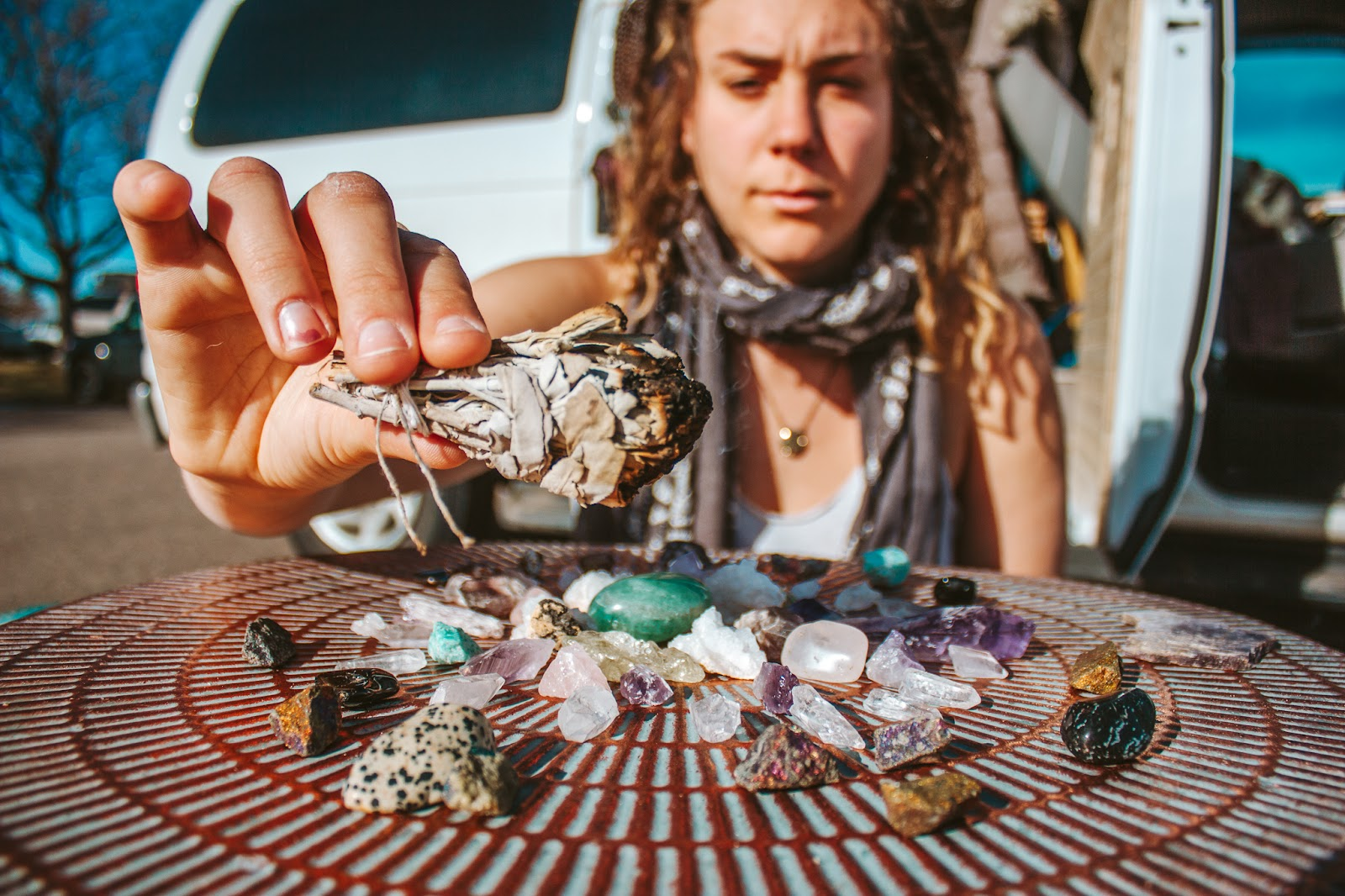 Holding burnt sage above gems and stones helps van life couples get rid of all the negative energy.