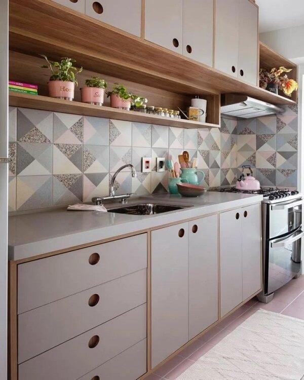 Cozinha com estilo delicado, armários em tons claros e com detalhes em madeira, azulejos com desenhos geométricos coloridos, acessórios rosas e verde.