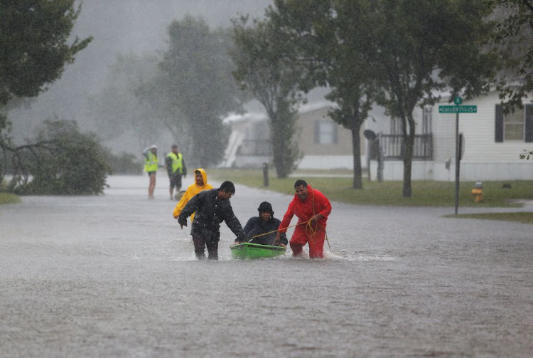 Residents help an elderly man evacuate a flooding trailer community during Hurricane Florence in Lumberton, North Carolina, on September 15 2018.