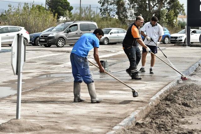 Trabajadores de una gasolinera limpiaban el barro.