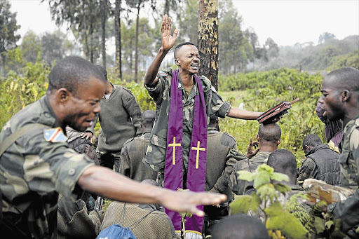 Congolese army chaplain Lieutenant-Colonel Aaron Kubuta prays with Congolese soldiers near the frontline as they try to push M23 rebels out of Goma