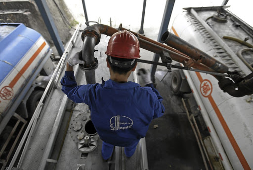 An employee fills the tank of a petrol delivery vehicle at a Sinopec refinery. Picture: REUTERS