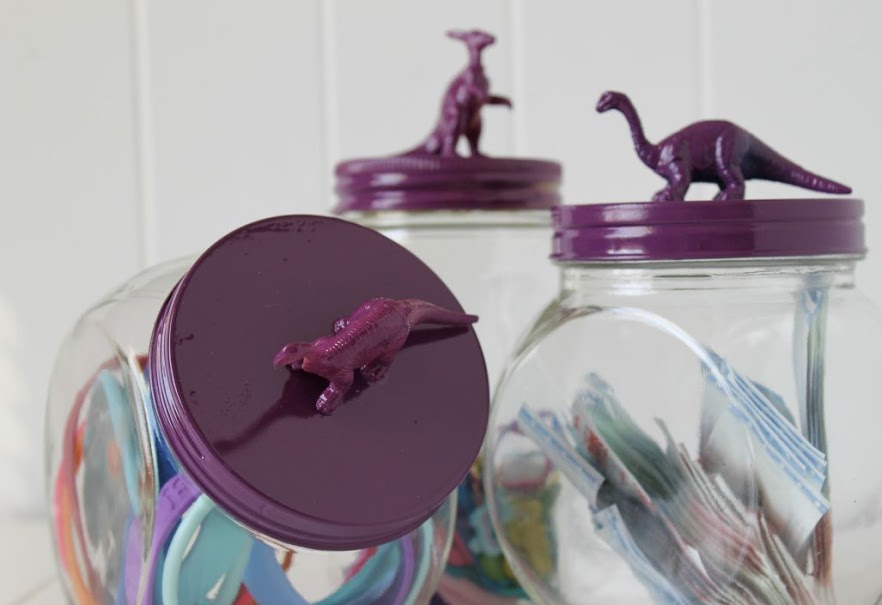 Once the paint on your lids is dry fill your jars with hair ties, adhesive bandages, jewelry - whatever you'd like. In addition to storage, they make easy and inexpensive kids bathroom decor, too.