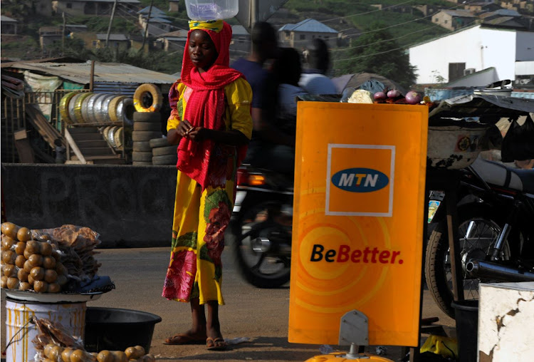 A woman stands near an MTN logo in Lokoja city, Kogi State, Nigeria September 17, 2018.
