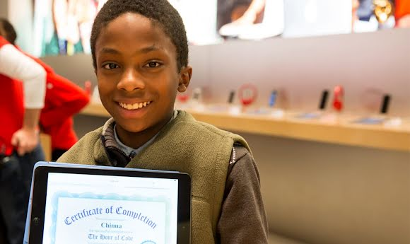 A Code.org student proudly shows off his certificate after completing a class.