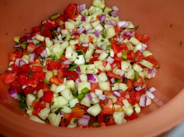 In a small bowl, combine the cucumbers, tomatoes, onion, parsley, jalapeno, cilantro and garlic.