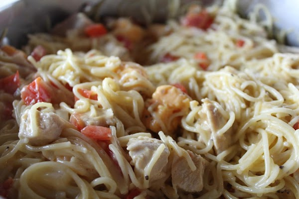 Cheese added to tomato, spaghetti and chicken mixture.