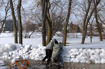 Photo: Spcs. Dan Francis, left, and Scott Nielson, both infantrymen from Company A, 2nd Combined Arms Battalion, 136th Infantry Regiment, adjust a pump to battle a breach in a sandbag wall as the Red River continues to rise in Moorhead, Minn., Friday, March 27, 2009. The Red River continues to rise as a result of rain and snowmelt and is expected to crest at 43 feet, three feet higher than the current flood record. More than 500 Minnesota National Guard Soldiers and Airmen have been called up to state active duty to assist local authorities with traffic control, security as well as other tasks.(U.S. Army photo by Staff Sgt. Jon Soucy)(released)
