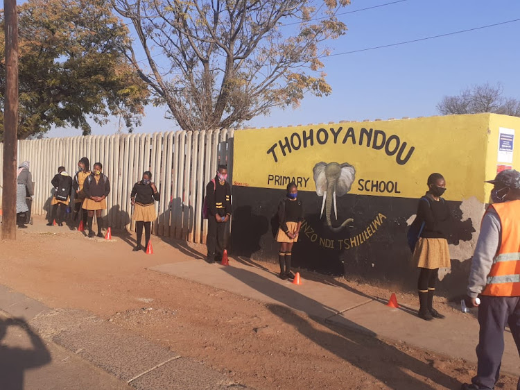 Masked grade 7 pupils at Thohoyandou Primary queue for their temperatures to be taken on their first day back at school.
