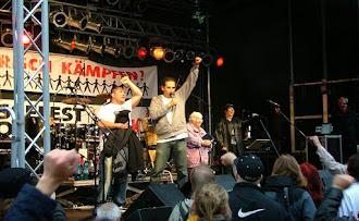 Künstler auf der Bühne mit erhobener Faust vor begeistertem Publikum.