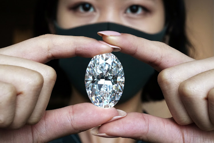 An employee of Sotheby's poses with a perfect 100+ carat diamond, the second largest oval diamond of its kind to ever appear at an auction, which will be auctioned by Sotheby's in Hong Kong on October 5, picture taken September 9 2020. Picture: REUTERS/CARLO ALLEGRI
