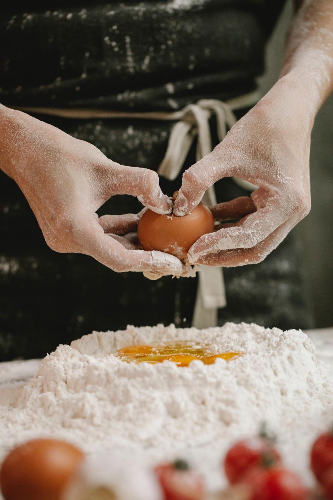 raw egg being mixed into flour - accordingtojo.com