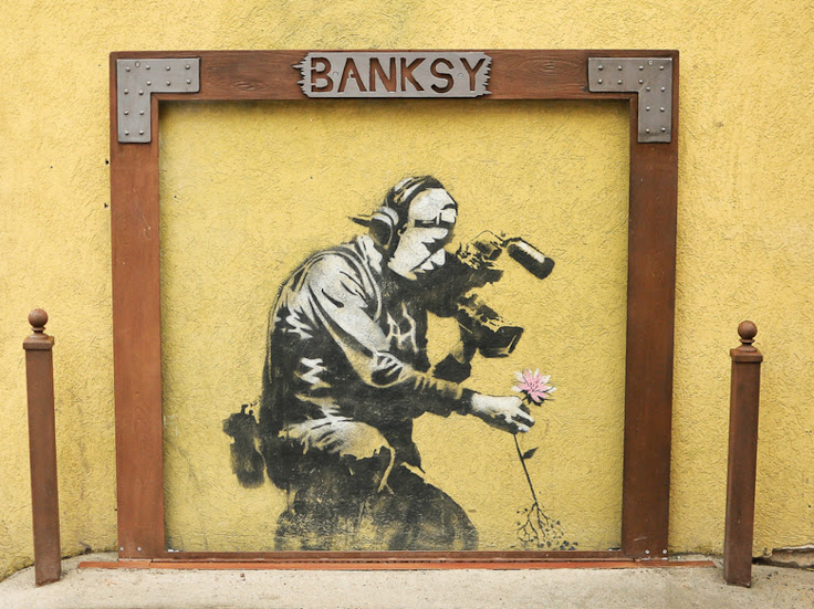 """Camera Man and Flower"" by Banksy at 402 Main St."