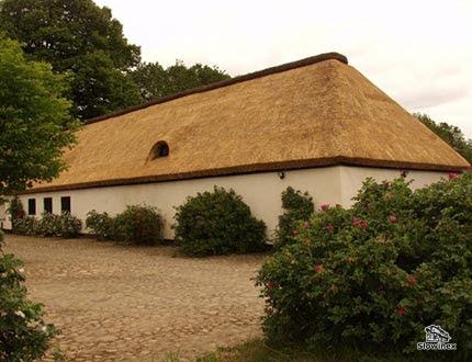 Podłużny budynek w kolorze kremowym z dachem ze strzechy w otoczeniu zieleni