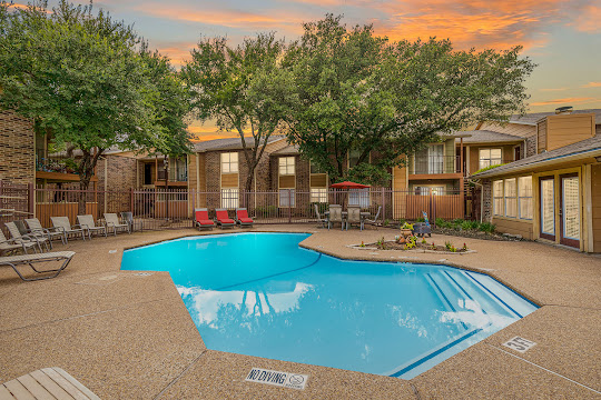 Bella Vista's swimming pool with picnic table and lounge chairs at dusk by apartment buildings