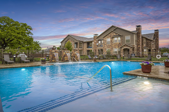 Mansions at Hickory Creek's resort-style swimming pool with waterfall feature at dusk