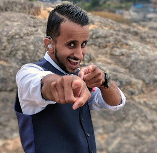 Narada grins playfully at the camera, pointing his fingers at the person shooting the picture. He is a young man wearing a collared white shirt, a black vest, and a hearing aid. He stands in front of a rocky landscape outside.