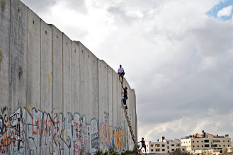 Photo: Young Palestinians use a ladder to scale the wall at Qalandiya checkpoint during clashes. (SOLD)