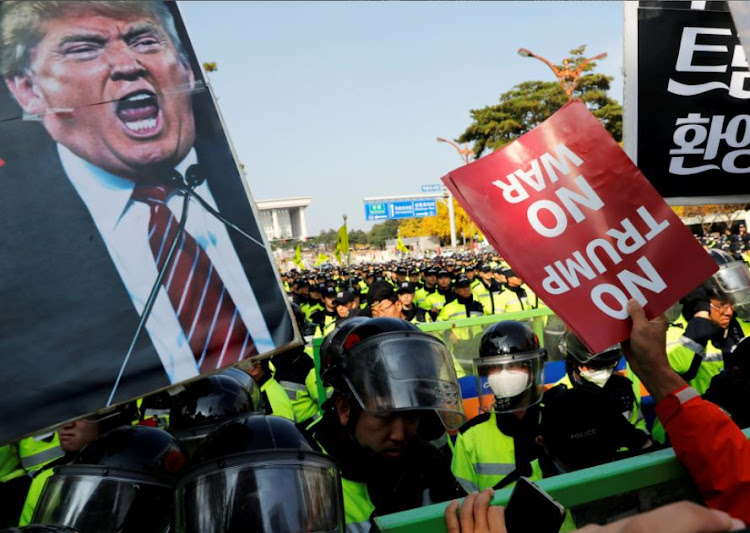 Anti-Trump protesters hold up signs in front of police officers near the South Korean National Assembly where U.S. President Donald Trump made a speech, in Seoul, South Korea, November 8, 2017.