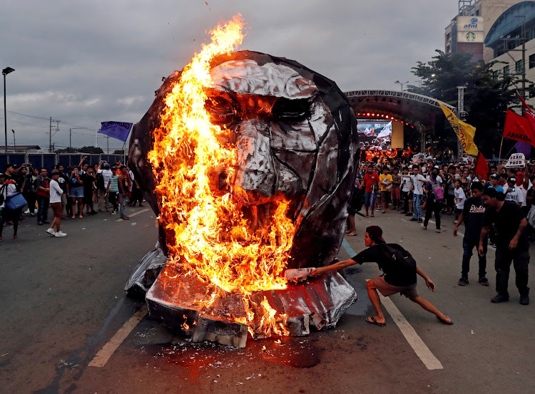 Activists burn an effigy of Philippine President Rodrigo Duterte while he delivers his State of the Nation address at the House of Representatives in the Philippines.