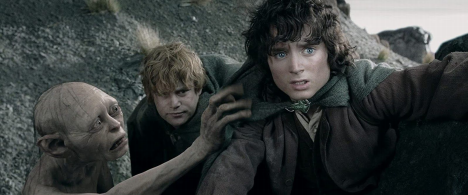Elijah Wood in The Lord of the Rings. Frodo stands on the side of a hill, crouched low. Behind him crouches Samwise, his blonde-haired gardener and companion on the quest. Beside Samwise is Gollum, a pallid bony creature with huge eyes and pointed ears, who reaches out to touch Frodo's shoulder.