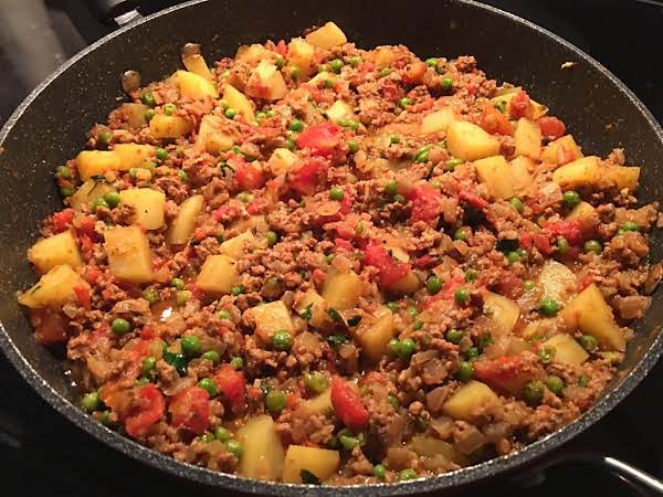 A Meat Casserole With Cubed Potatoes, Tomatoes And Peas.