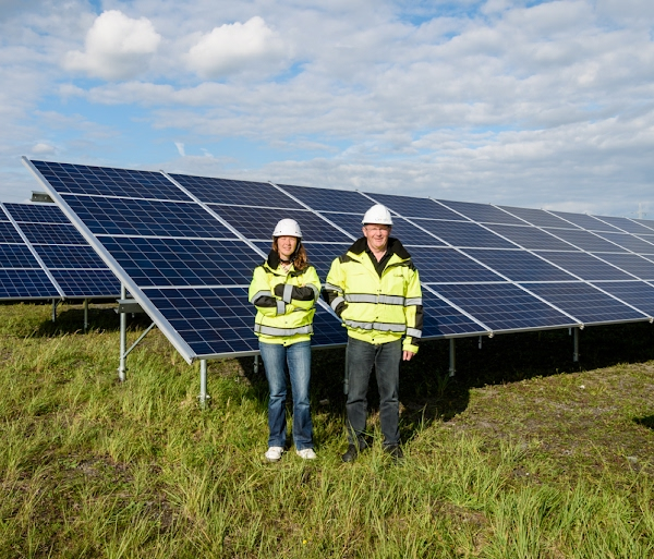 People in front of solar panel