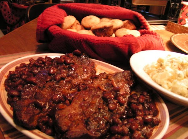 A plate of ribs and biscuits.
