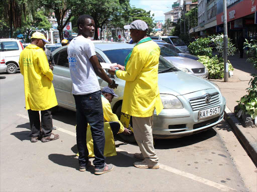 Ticketing officers clamp down a vehicle, whose owner had not paid for parking outside Simmers Restaurant on December 28 last year /COLLINS KWEYU