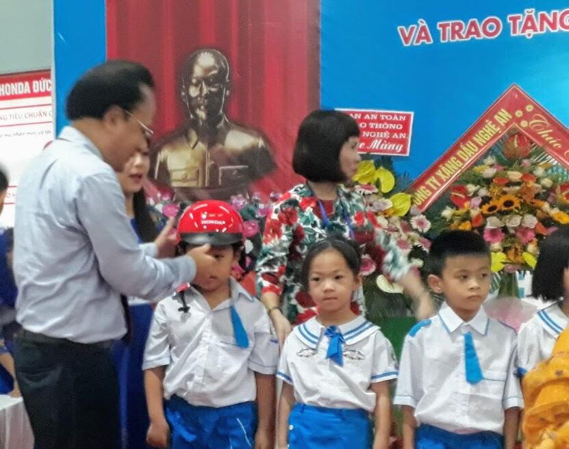 Đồng chí Nguyễn Nam Đình - Ủy viên Ban Thường vụ Tỉnh ủy, Bí thư Đảng ủy Khối Các cơ quan tỉnh trao mũ bảo hiểm cho học sinh Trường Tiểu học Hưng Lộc