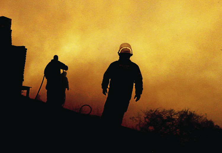 Firefighters battle to save a house in Buffalo Bay near Knysna as the fires along the Garden Route flared up again, fanned by gale-force winds.
