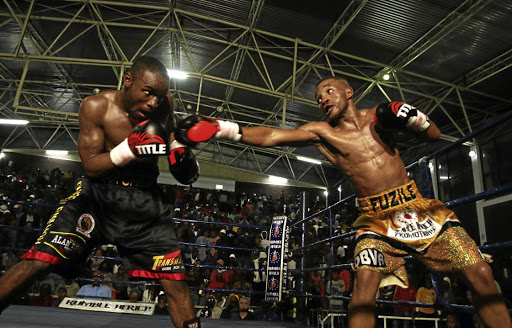 Rofhiwa 'War Child' Maemu tries to avoid a straight right from Azinga 'Golden Boy' Fuzile during their South African featherweight bout on July 30 last year, which Fuzile won.