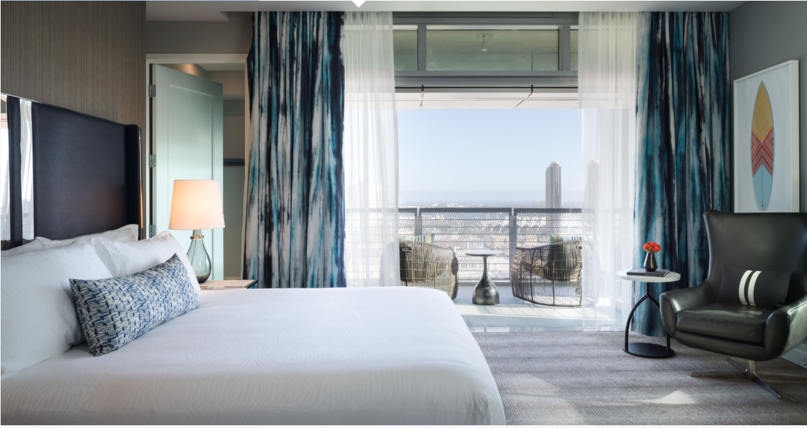 Hotel Room with city view, White bed with blue accents