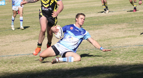 Narrabri Blues five eighth Hayden Bell slides in for one of his side's 14 tries at Collins Park on Saturday afternoon in its minor semi-final win against Collegian Warriors.