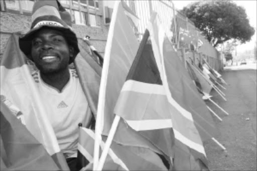 HAPPY MAN: Zimbabwean Austin Chikovo is now able to support his family selling the national flags of countries participating in the Fifa World Cup. PIC: THULI DLAMINI. 20/05/2010. © Sowetan.