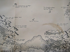 Photo: By being intentionally rough with my treatment of this map, I've left it in a slightly more delicate state than usual. (I wasn't worried about whether the ink would hold up, since I already knew that I could apply watercolors over it.) The effect was worth it in the end - especially in this desert. When it was stark black-on-white, this part of the map was just screaming for me to add something else. But I resisted until getting a look at the finished product, and by leaving this space open I've clearly ended up with something much better balanced and visually interesting than if I had kept throwing ink into this area.